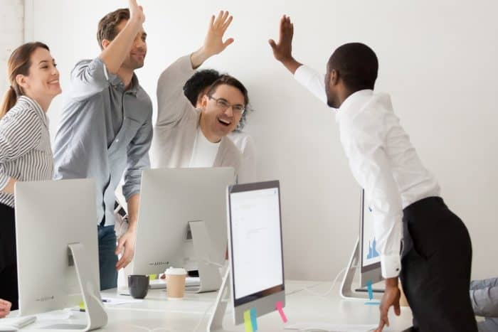 Happy Multi-ethnic Employees Sales Team Giving High Five Togethe